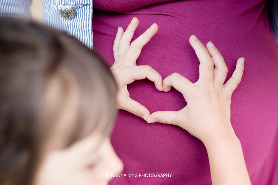Little girl making a heart shape with her fingers