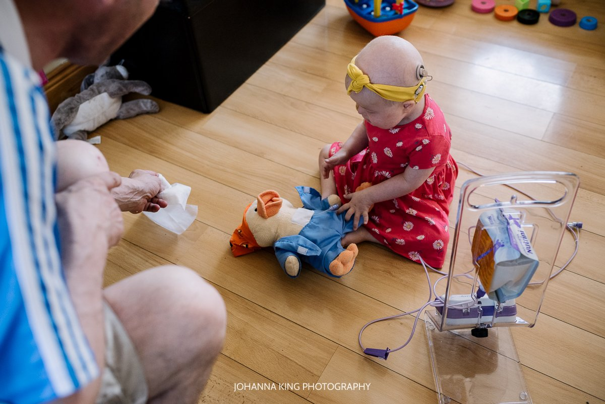 Réiltín playing with chemo duck, a soft toy receiving chemo like her